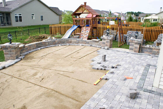 a backyard that has been half paved with stacks of pavers ready to be laid down around it by paving Ballarat