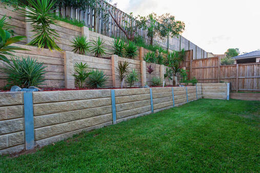 a backyard with a 3 level retaining wall system with printed concrete sleepers