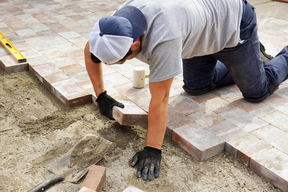 a paving Ballarat worker laying down some pavers with black gloves on and a level close by