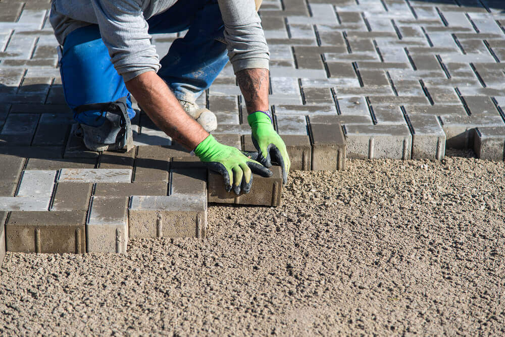 a paving Ballarat worker with green safety gloves on laying a single brick amongst many other bricks that have been laid
